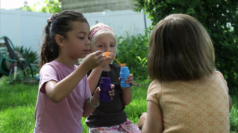 Slow handheld shot of three little girls blowing bubbles Live Action