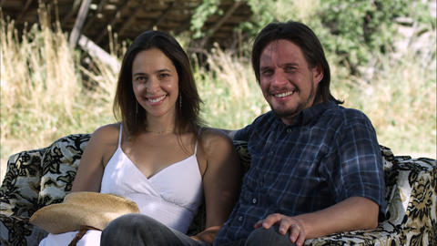 Slow static shot of a couple smiling and looking at the camera while sitting on  Footage