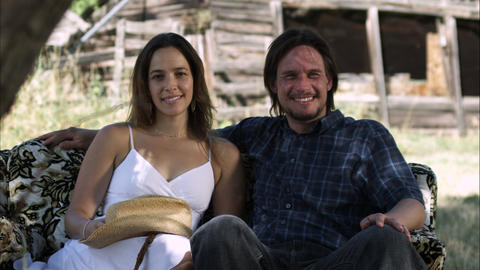 Slow dolly shot of a couple smiling and looking at the camera while sitting on a Footage