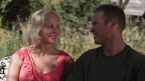 Tracking shot of a beautiful couple talking and smiling outdoors in slow motion Footage