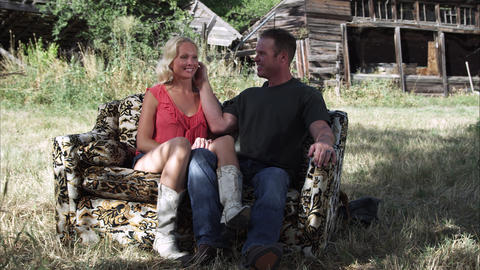 Slow dolly shot of an affectionate couple sitting on a couch outdoors at a farm Live Action