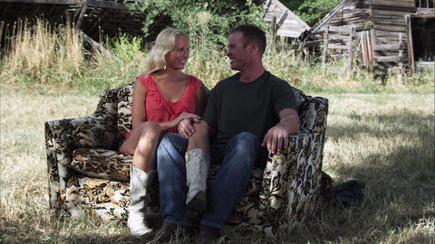 Slow tracking shot of an affectionate couple talking on a couch outdoors at a fa Footage