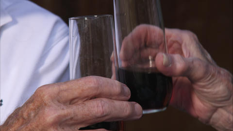 Slow close-up shot of hands of two elderly people clinking glasses Footage