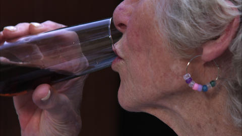 Slow motion handheld close-up shot of an elderly woman drinking wine Footage