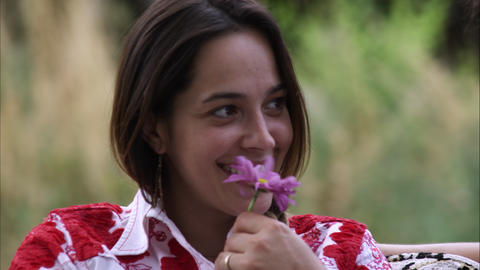 Close-up dolly shot of young woman receiving a purple flower from a man Live Action