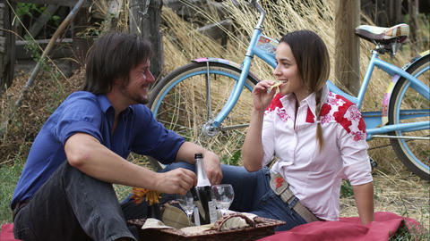 Slow tracking shot of a young couple having an outdoor picnic Footage