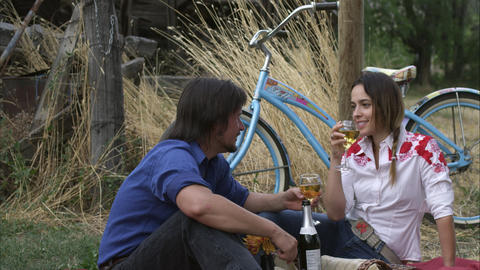 Slow close-up tracking shot of a young couple enjoying white wine at an outdoor  Footage