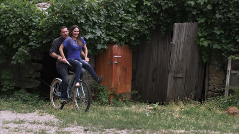 Slow motion, tracking shot of a couple riding a bicycle Footage