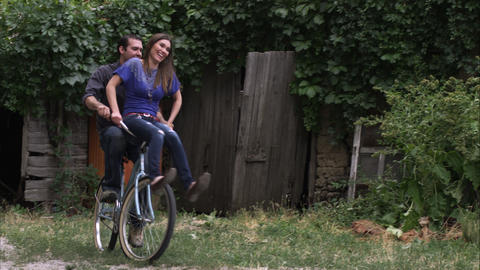 Slow motion, tracking shot of a couple riding a bicycle together Footage