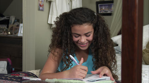 Slow motion pan of girl thinking of what to write in diary Footage