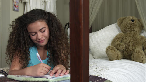 Slow motion pan of girl writing in diary then looking up to smile Footage