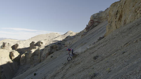 Slow motion of guy riding mountain bike off rocky cliff down a steep rocky slope Footage