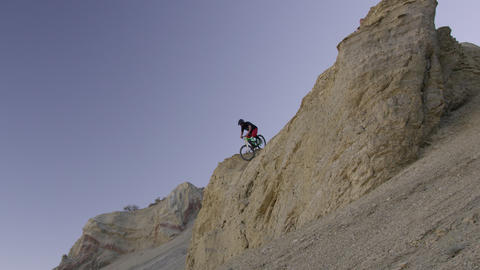 Slow motion of guy riding mountain bike off rocky cliff down a steep rocky slope Live Action
