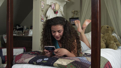 Slow motion of girl texting lying on her bed Live Action