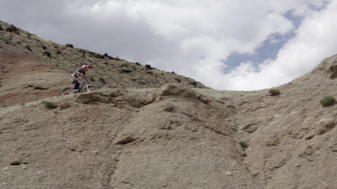 Slow motion of a guy riding mountain bike down hill and hitting jump Footage