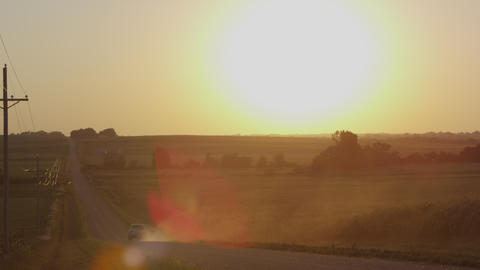 Static view of fields with the sun above the horizon, as truck drives by Footage