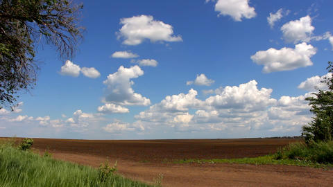 Blue sky over plowed field Footage