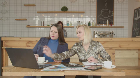 Two businesswomen networking with gadgets in cafe Live Action