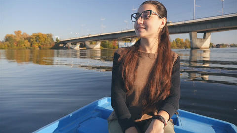 Beautiful girl sailing on the river in a boat. A joyful smile. Beautiful Footage