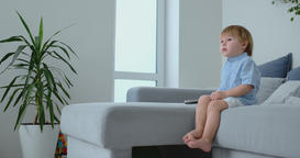 A 2 years old boy sits on a sofa and watches TV sitting with a remote control in Footage