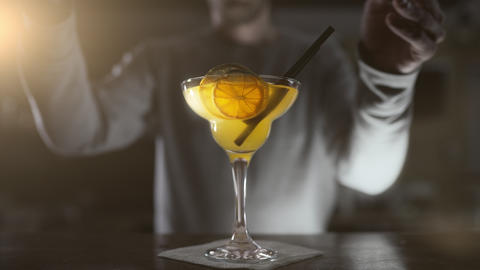 Bartender finishes the cocktail in high glass with dried fruits and cocktail Footage