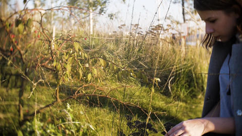 young teen girl looking at dried grass in the park on a sunny day GIF