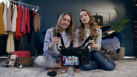 Two female fashion blogger demonstrating trend shoes for making video blog about Live Action