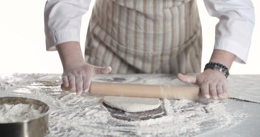 Baker kneading dough with rolling pin on table Footage