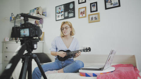Young attractive girl fashion blogger is recording video with camera, singing Footage