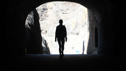 Camera follows a woman silhouette walking through dark tunnel towards the light Footage
