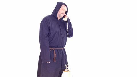 man in monk hoodie speaking by vintage phone white screen Footage