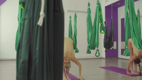 Two women doing warm-up exercises before aerial yoga class Footage