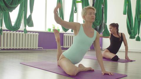 Two flexible women doing yoga exercises in nice studio Live Action