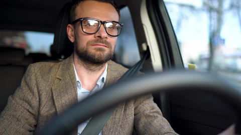 Satisfied bearded man in glasses driving a car down the street in sunny weather Footage