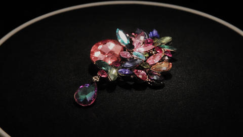 Colored brooch on a black rotating stand. Premium Jewelery Footage