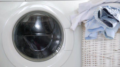 Laundry is washed in the washing machine, and clean things are on the basket Footage