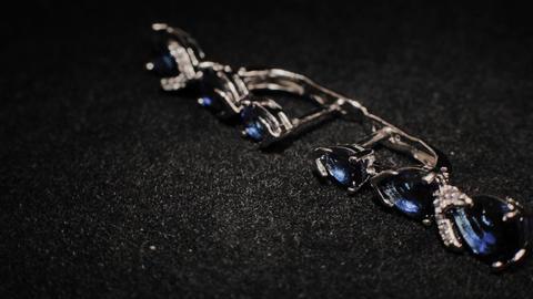 Beautiful female earrings on a black rotating stand. Premium Jewelery. Macro Footage