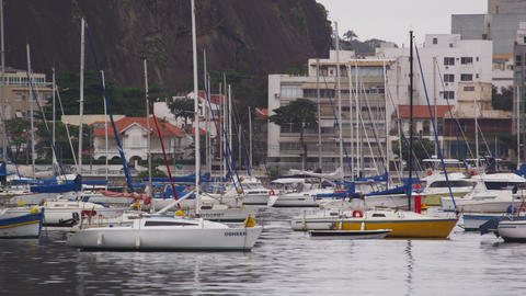 Panning shot of marina with several boats along the coastline in Rio de Janeiro, Footage