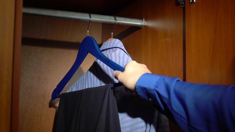 Placing pants and a shirt into a wardrobe Footage