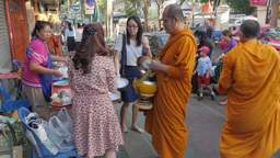 Woman give offerings and prays with monk on street,Bangkok,Thailand Footage
