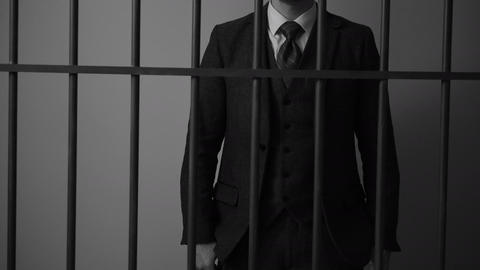 A white collar criminal stands behind bars in jail Live Action