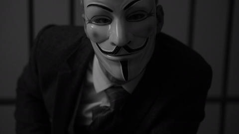 Anonymous hacker man stares into camera in prison (B/W Version) Footage