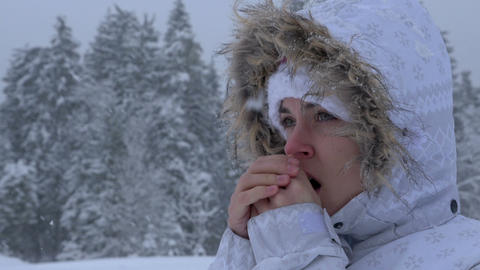 Young woman warming up her hands by breath in a winter background Live Action