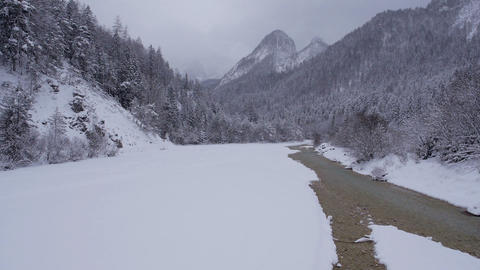 Aerial - Snow covered mountain region with a river cutting through the landscape Footage
