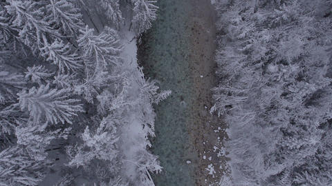 Aerial, vertical - River through the winter forest at a light snowing Footage