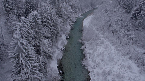 Aerial - River through the winter forest at a light snowing Footage
