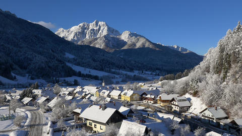 Aerial - Snowy village beneath beautiful sunlit mountain Footage