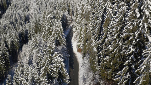 Aerial - Tilting up from road to panoramic view of winter landscape Footage