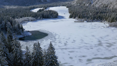 Aerial - Tilt up from panoramic view at frozen lake to the mountains Footage