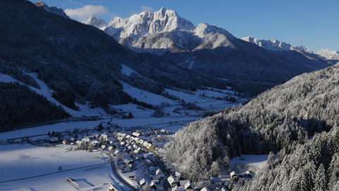 Aerial - Snowy village beneath beautiful sunlit mountain, long shot Footage